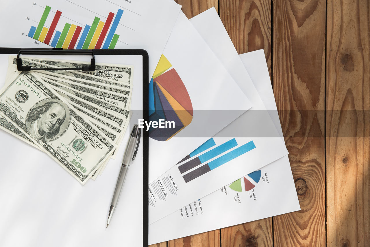 High angle view of documents with money on table