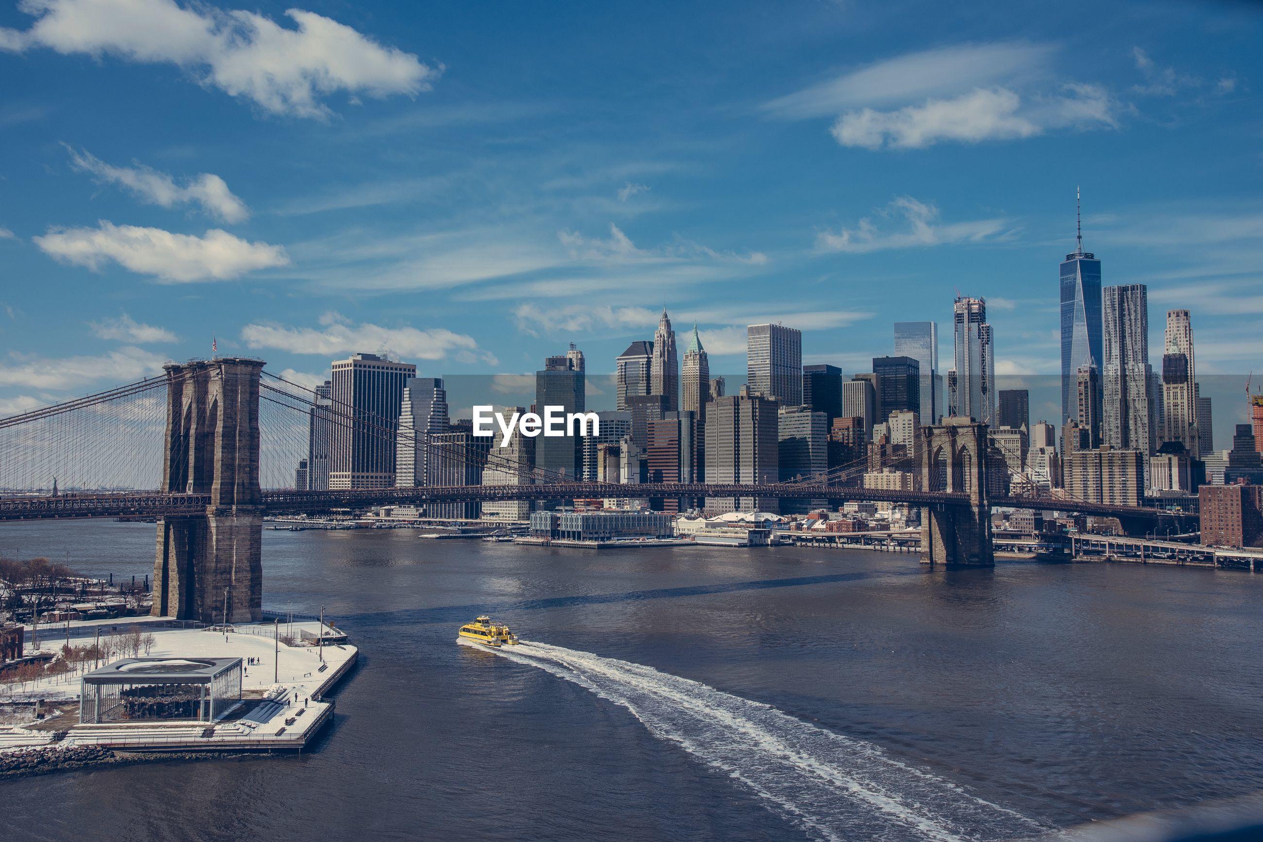 Brooklyn bridge over river by modern buildings against sky