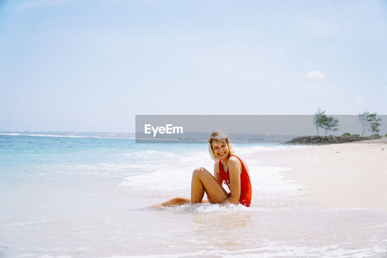 Portrait of smiling young woman sitting at beach against sky