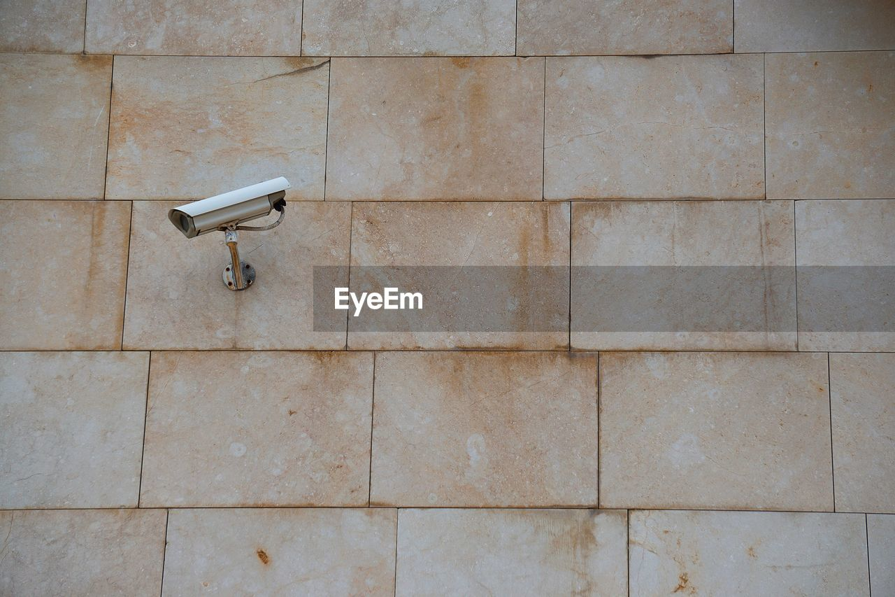 security camera, surveillance, wall - building feature, no people, built structure, architecture, security, security system, safety, protection, technology, day, pattern, outdoors, control, tile, close-up, shape, wall, stone wall, big brother - orwellian concept
