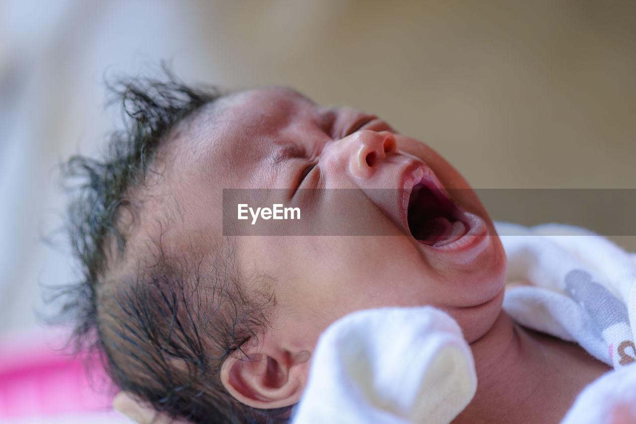 Close-Up Of Baby Girl Crying At Home