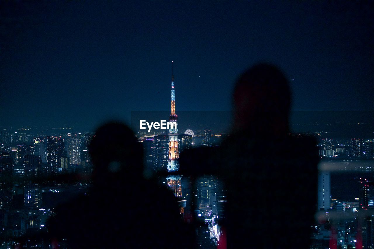 Silhouette people standing against illuminated tokyo tower in city at night