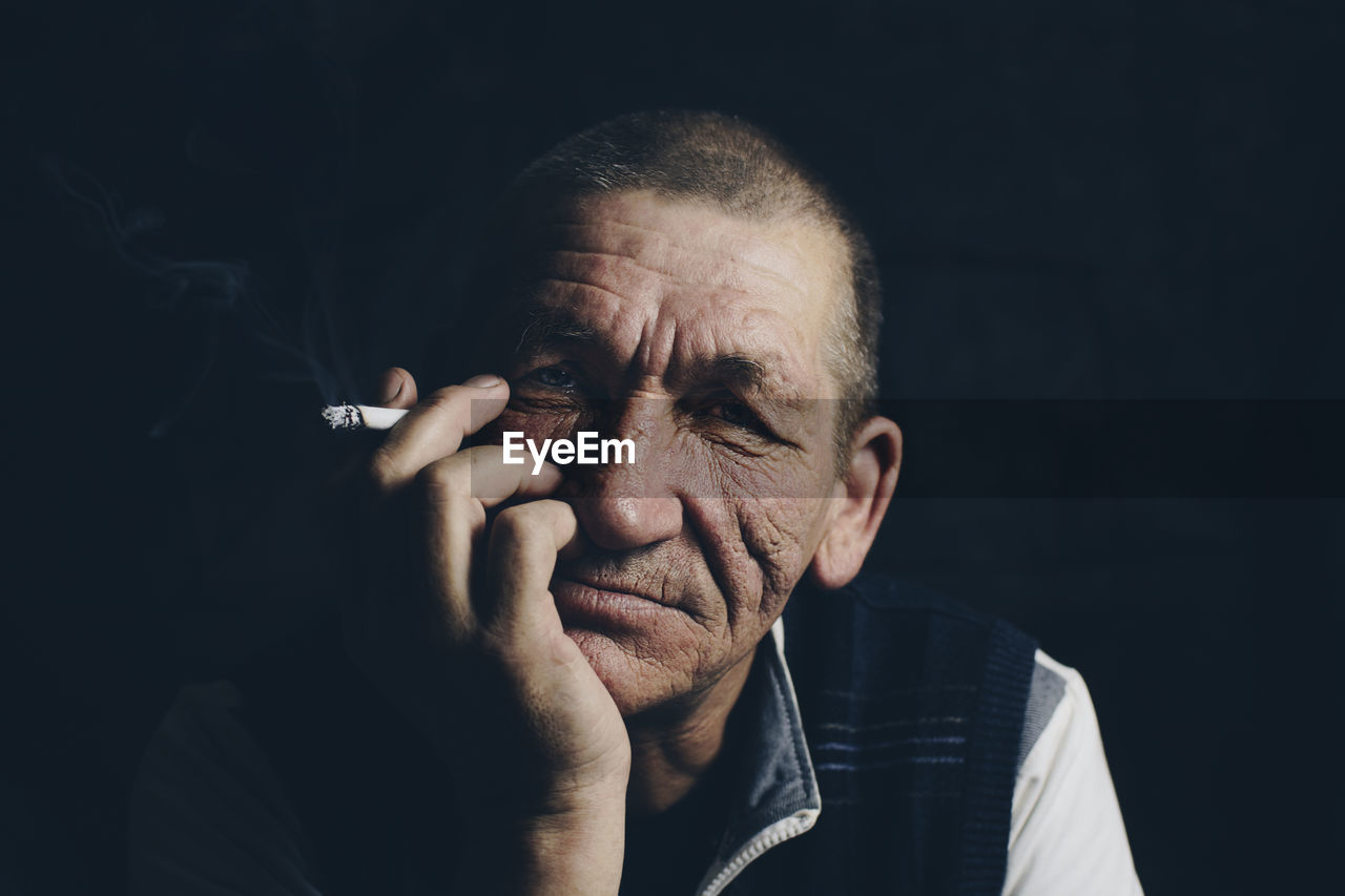 Close-up portrait of man smoking cigarette against black background