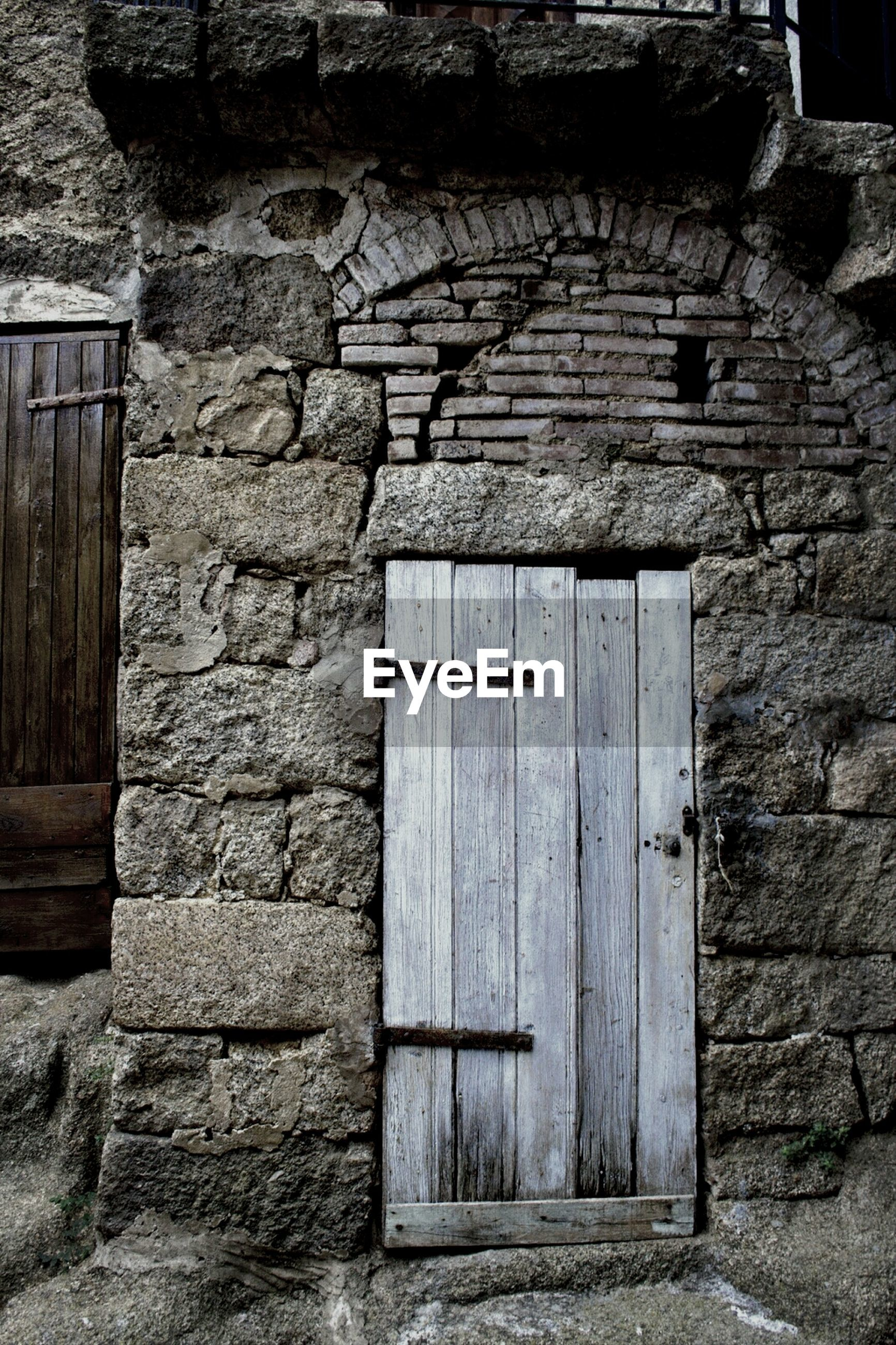 architecture, built structure, building exterior, brick wall, stone wall, old, door, wall - building feature, house, closed, weathered, entrance, window, abandoned, wood - material, wall, protection, damaged, outdoors, safety