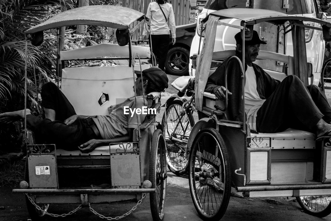 real people, transportation, mode of transportation, land vehicle, men, sitting, people, day, city, lifestyles, rickshaw, street, road, casual clothing, cart, outdoors, full length, adult