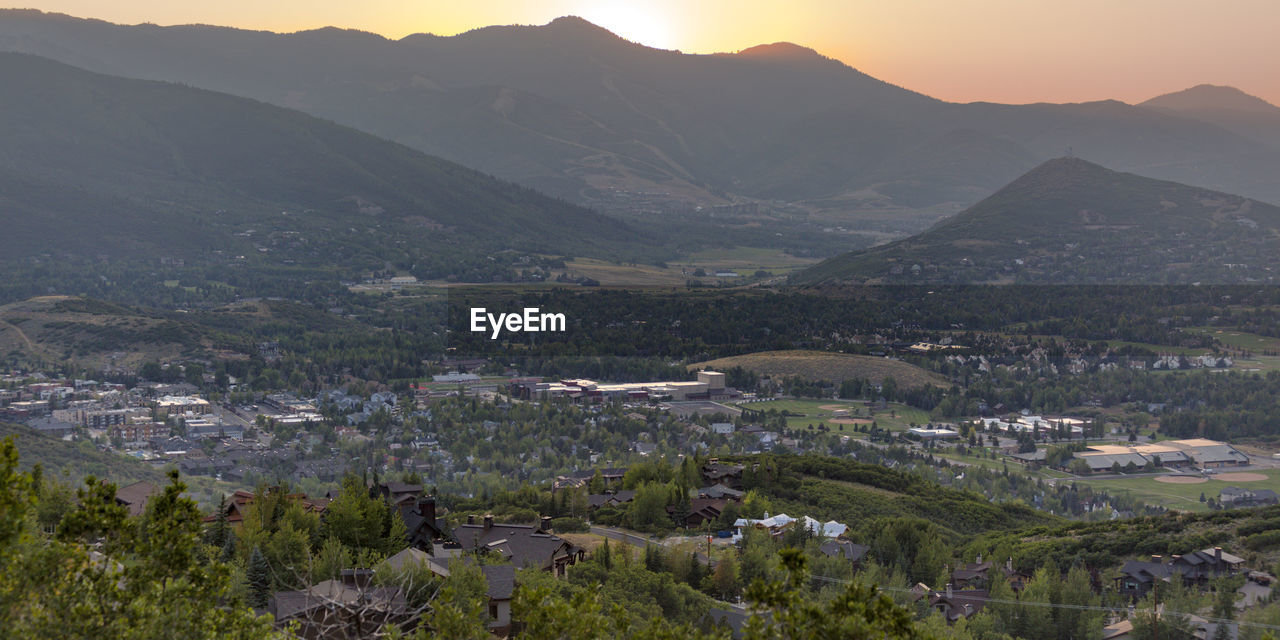 AERIAL VIEW OF TOWNSCAPE AGAINST MOUNTAINS