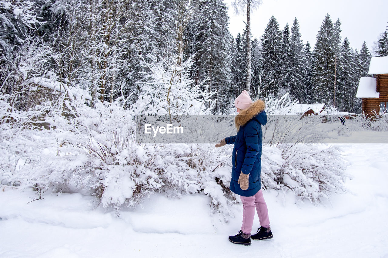 snow, winter, cold temperature, tree, nature, clothing, footwear, one person, plant, full length, warm clothing, child, land, leisure activity, day, childhood, white, beauty in nature, environment, standing, freezing, forest, holiday, hat, outdoors, pinaceae, landscape, coniferous tree, scenics - nature, snowshoe, female, adult, pine tree, women, lifestyles, non-urban scene, nordic skiing, vacation, frozen, fun, mountain