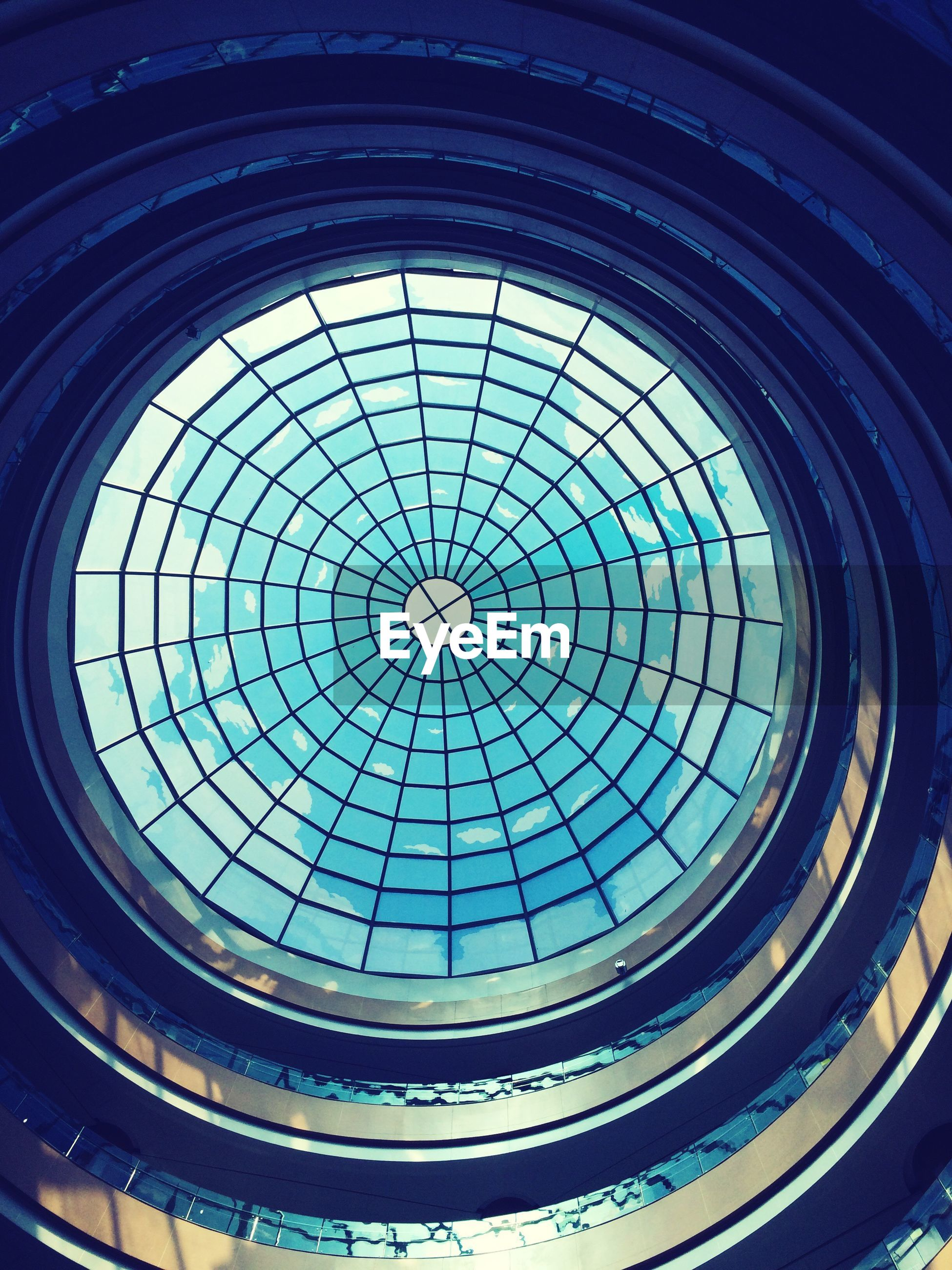 indoors, architecture, low angle view, built structure, pattern, ceiling, skylight, design, architectural feature, glass - material, directly below, geometric shape, window, dome, circle, full frame, backgrounds, repetition, no people, modern