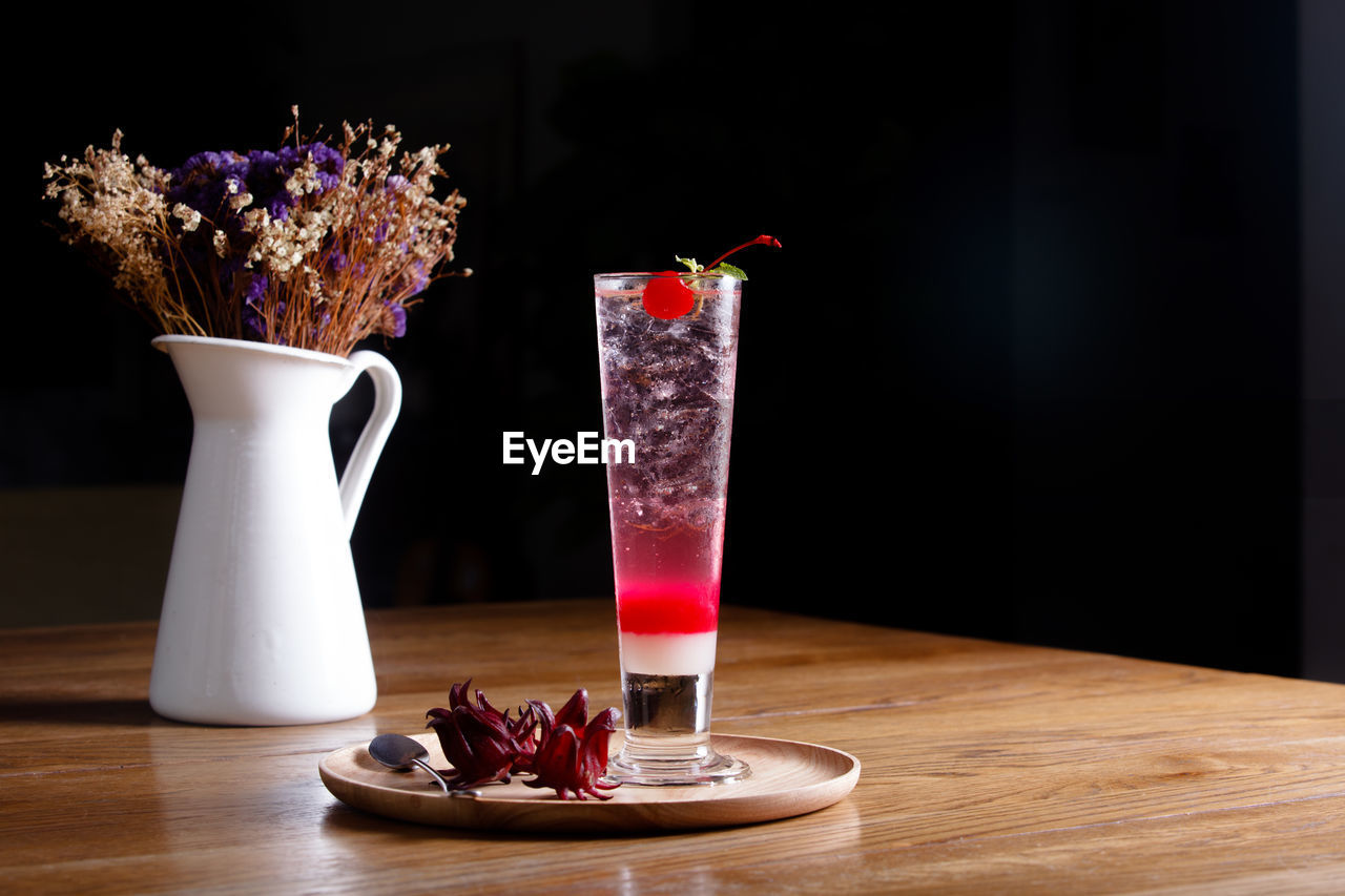table, food and drink, freshness, flower, food, flowering plant, indoors, vase, still life, glass, drinking glass, no people, drink, red, berry fruit, household equipment, wood - material, nature, refreshment, plant, black background, temptation, flower arrangement