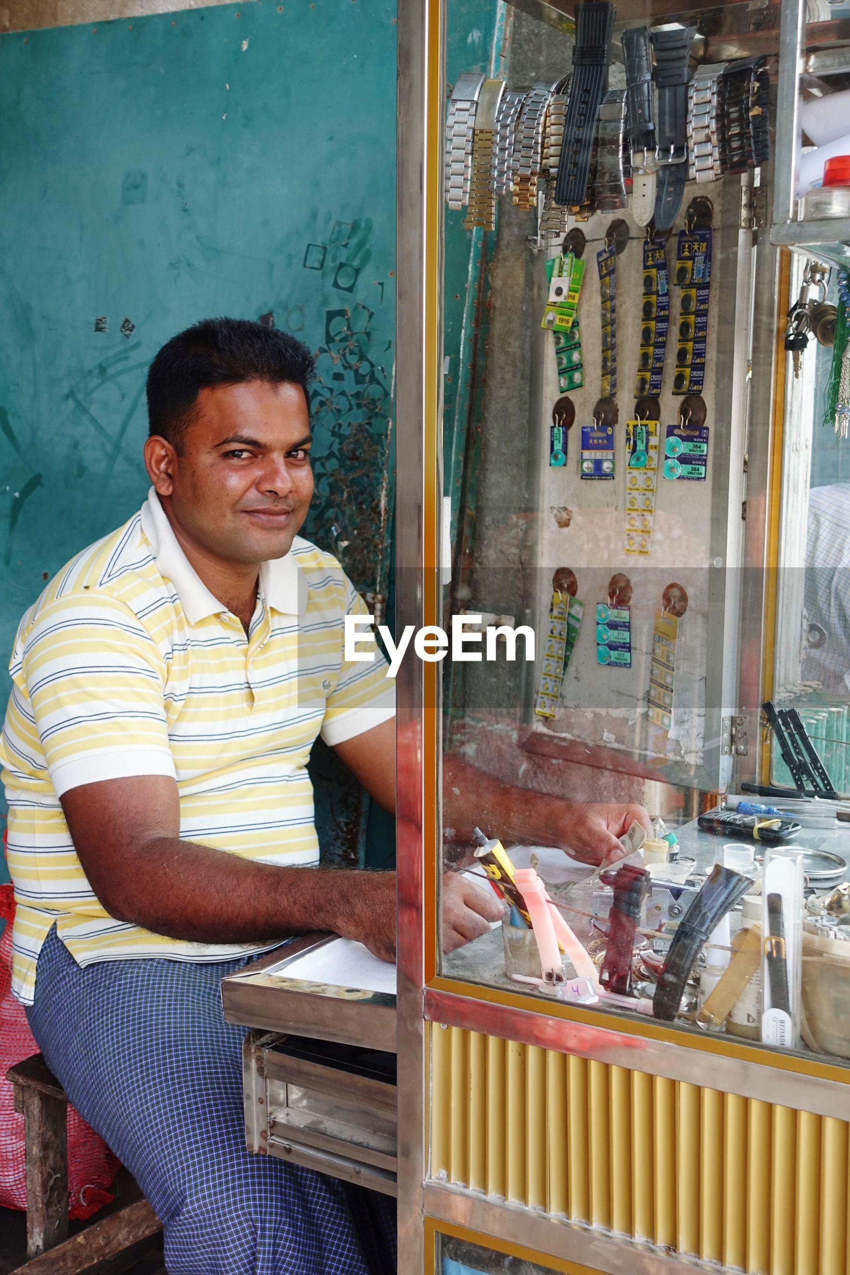 Portrait of smiling man sitting at wristwatch repair store