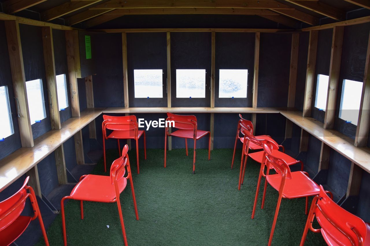 red, chair, seat, absence, empty, indoors, no people, table, arrangement, day, restaurant, in a row, business, architecture, order, furniture, side by side, window, group of objects, setting