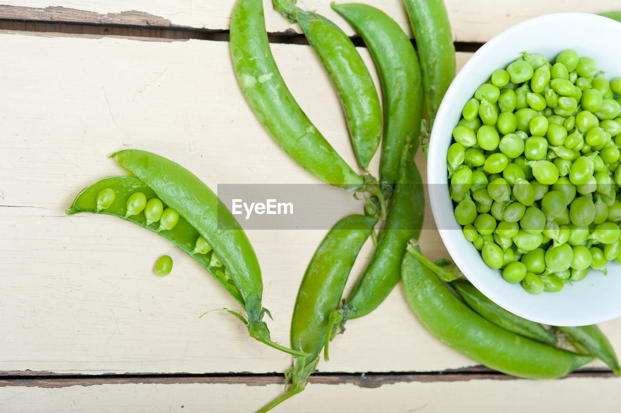 High angle view of green peas by bowl on wooden table