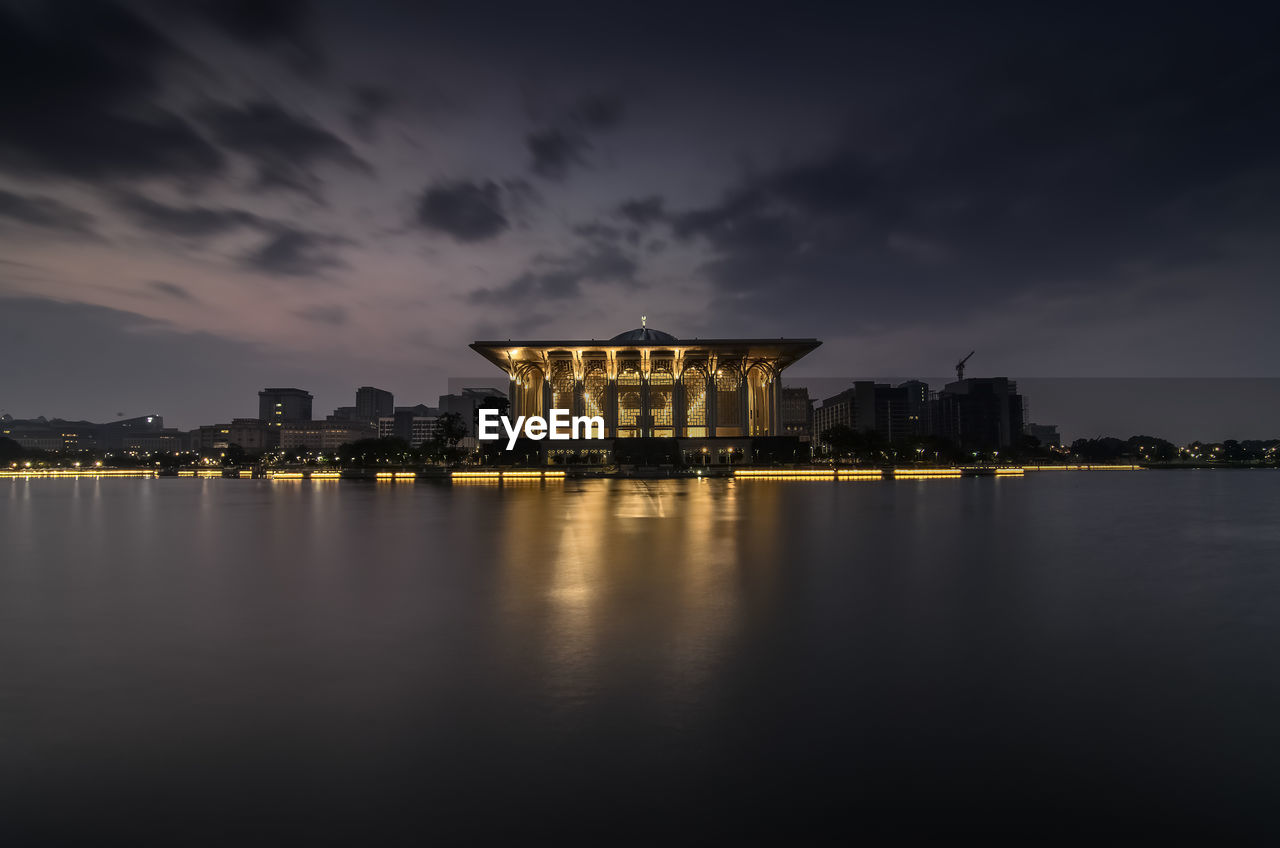 Illuminated iron mosque and lake against cloudy sky during sunrise