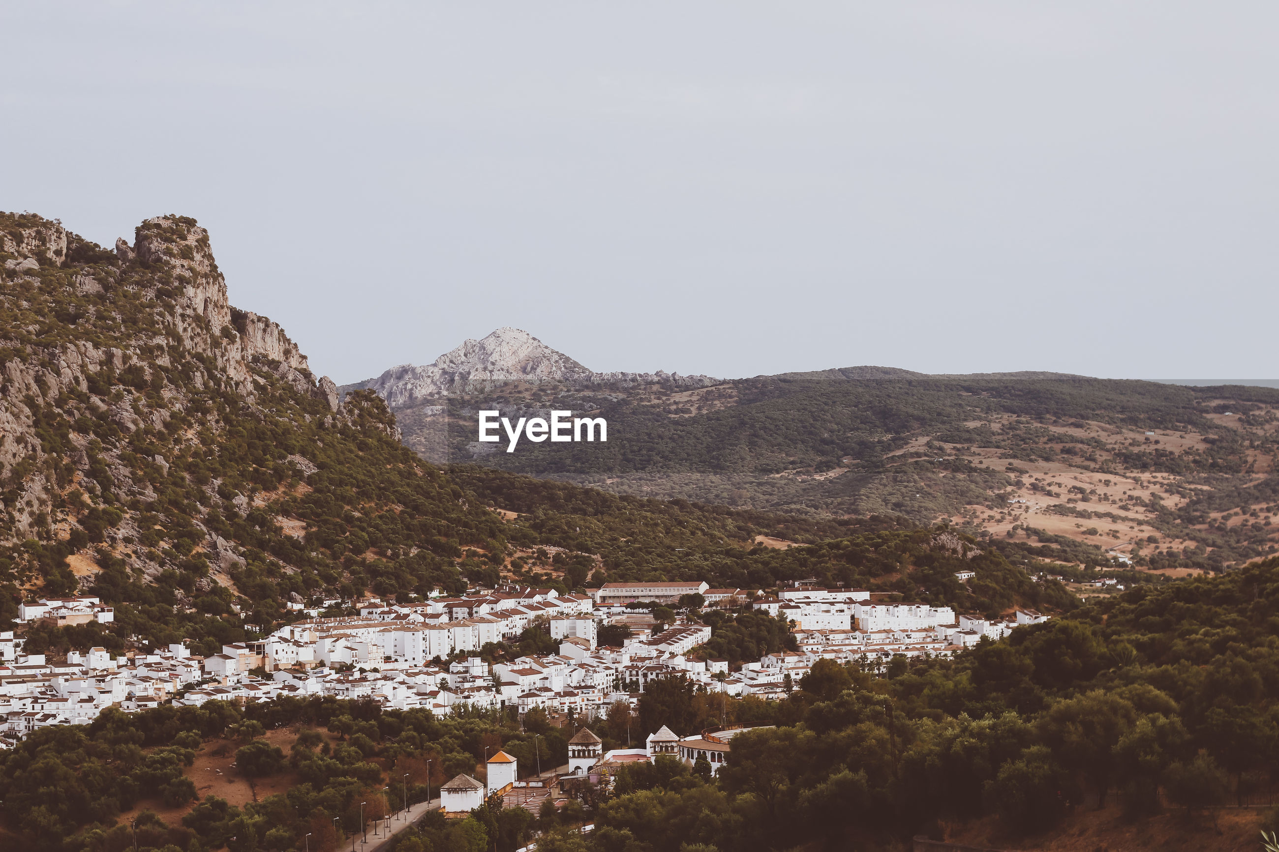 Town by mountain against clear sky