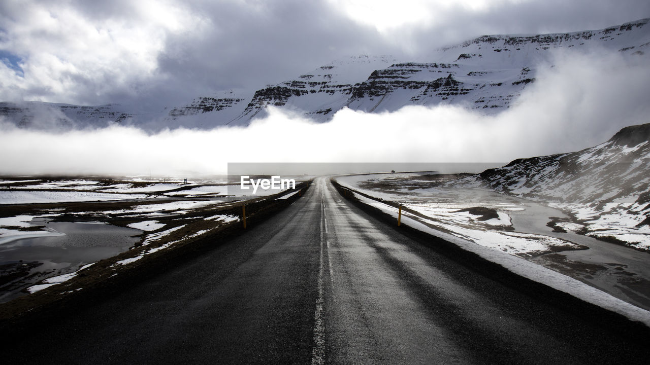 PANORAMIC VIEW OF SNOWCAPPED ROAD AGAINST SKY