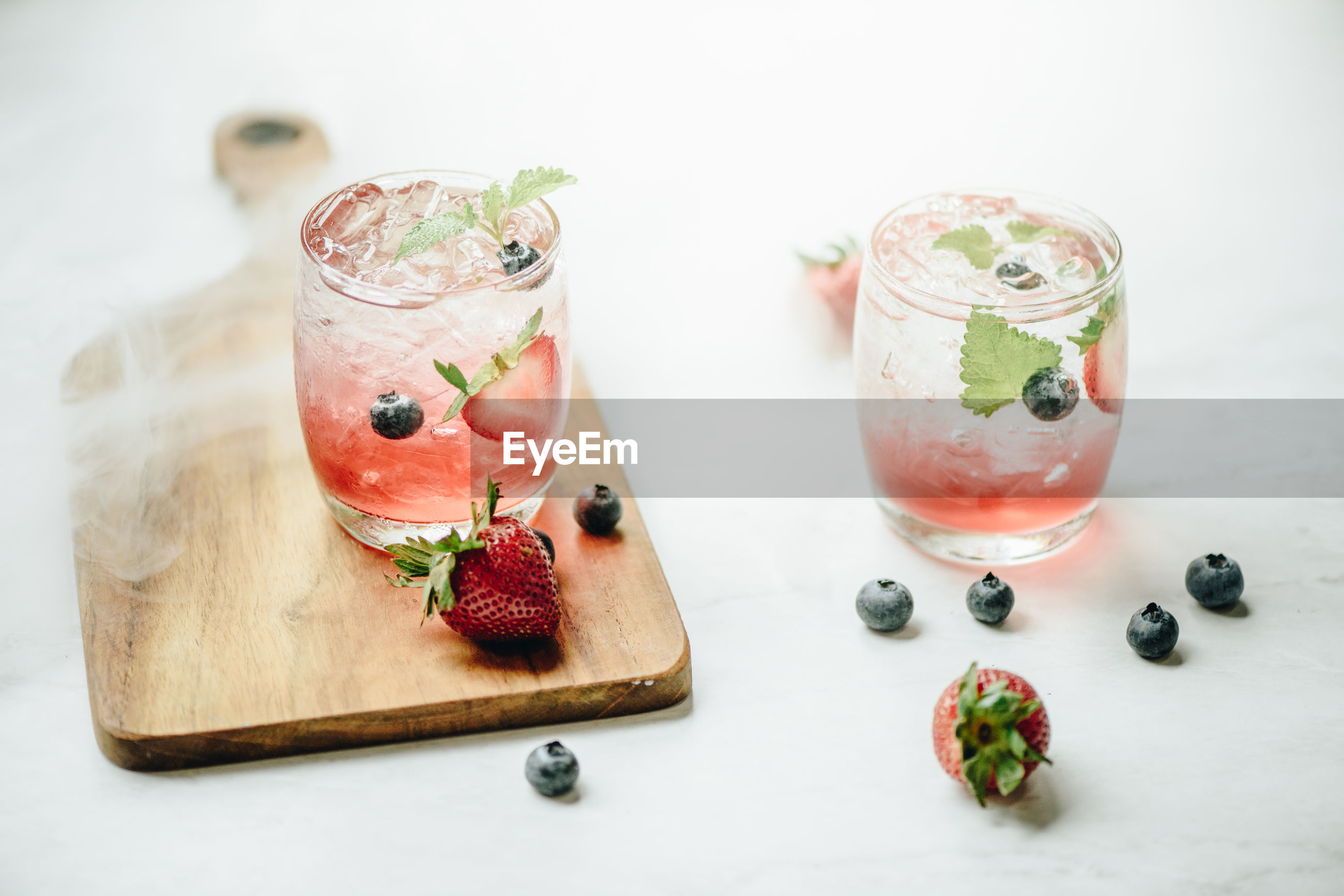 Close-up of drinks with strawberries and blueberries served on table