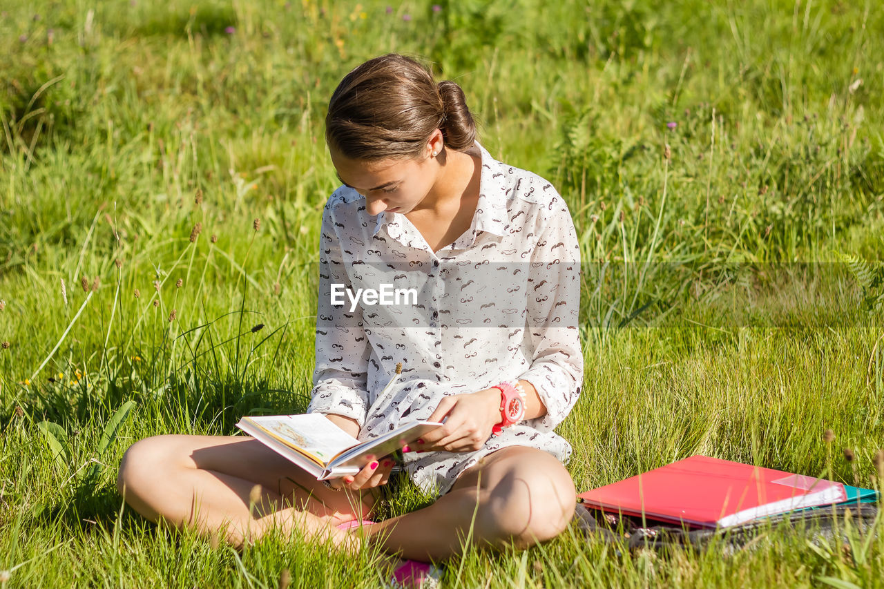 Full length of woman reading book while sitting on field
