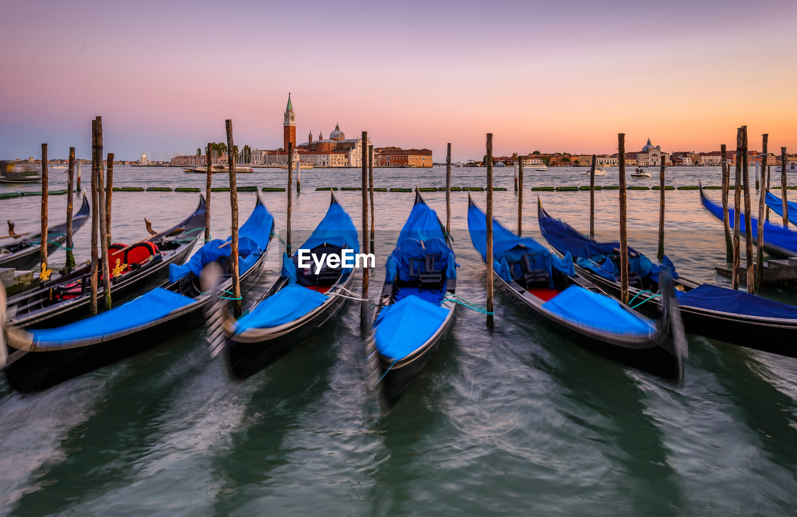 Boats moored at sea against sky during sunset