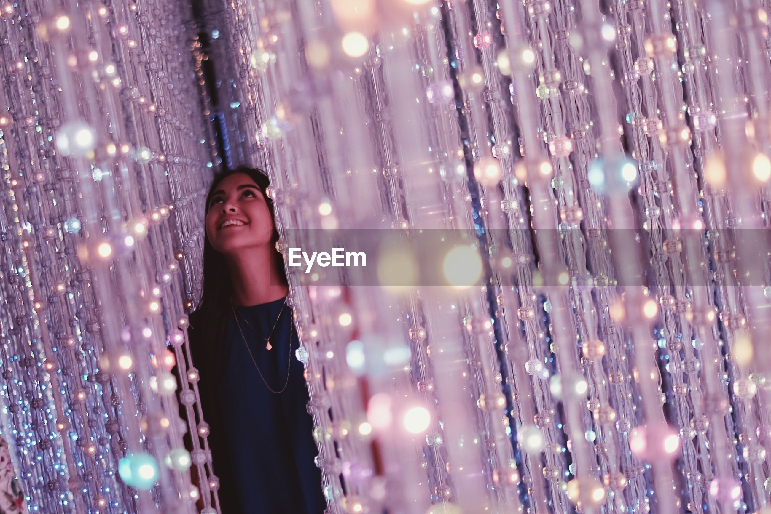 focus on foreground, lifestyles, leisure activity, illuminated, celebration, lens flare, selective focus, night, standing, close-up, defocused, tree, enjoyment, outdoors, three quarter length, front view, motion, holding