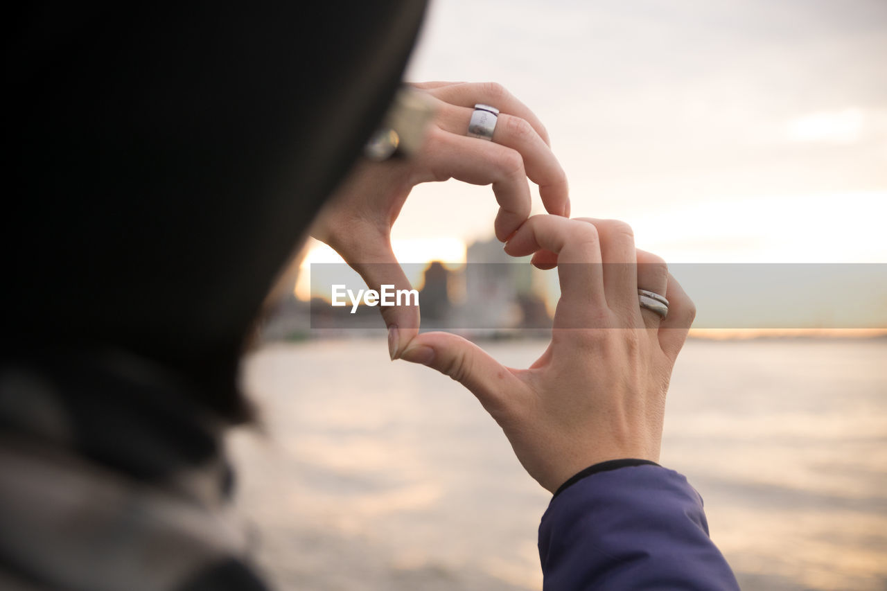 Close-up of woman hands making heart shape against sea during sunset