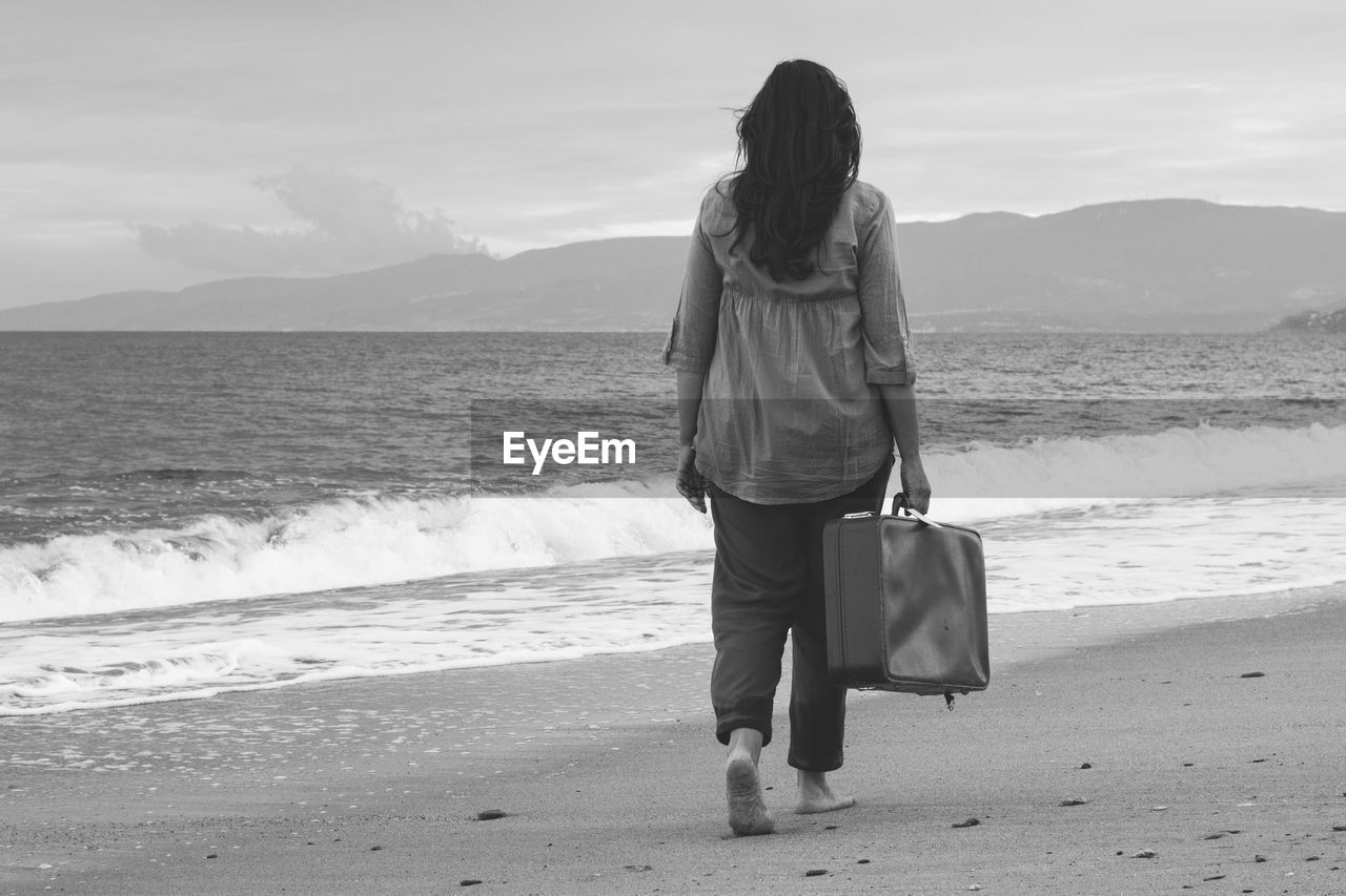 Rear view of woman holding suitcase while walking at beach