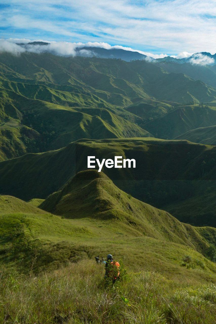 mountain, scenics - nature, beauty in nature, landscape, environment, mountain range, tranquil scene, tranquility, grass, nature, adventure, non-urban scene, plant, day, leisure activity, green color, real people, hiking, sky, cloud - sky, outdoors, mountain peak
