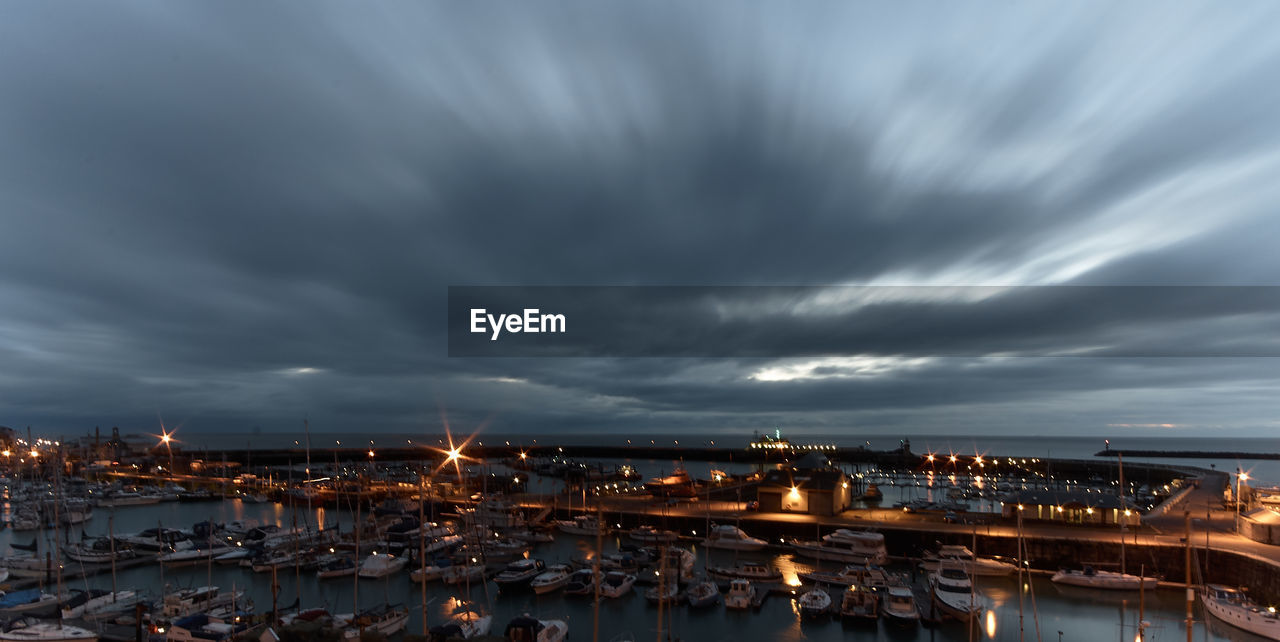 Boats Moored At Harbor Against Cloudy Sky During Dusk