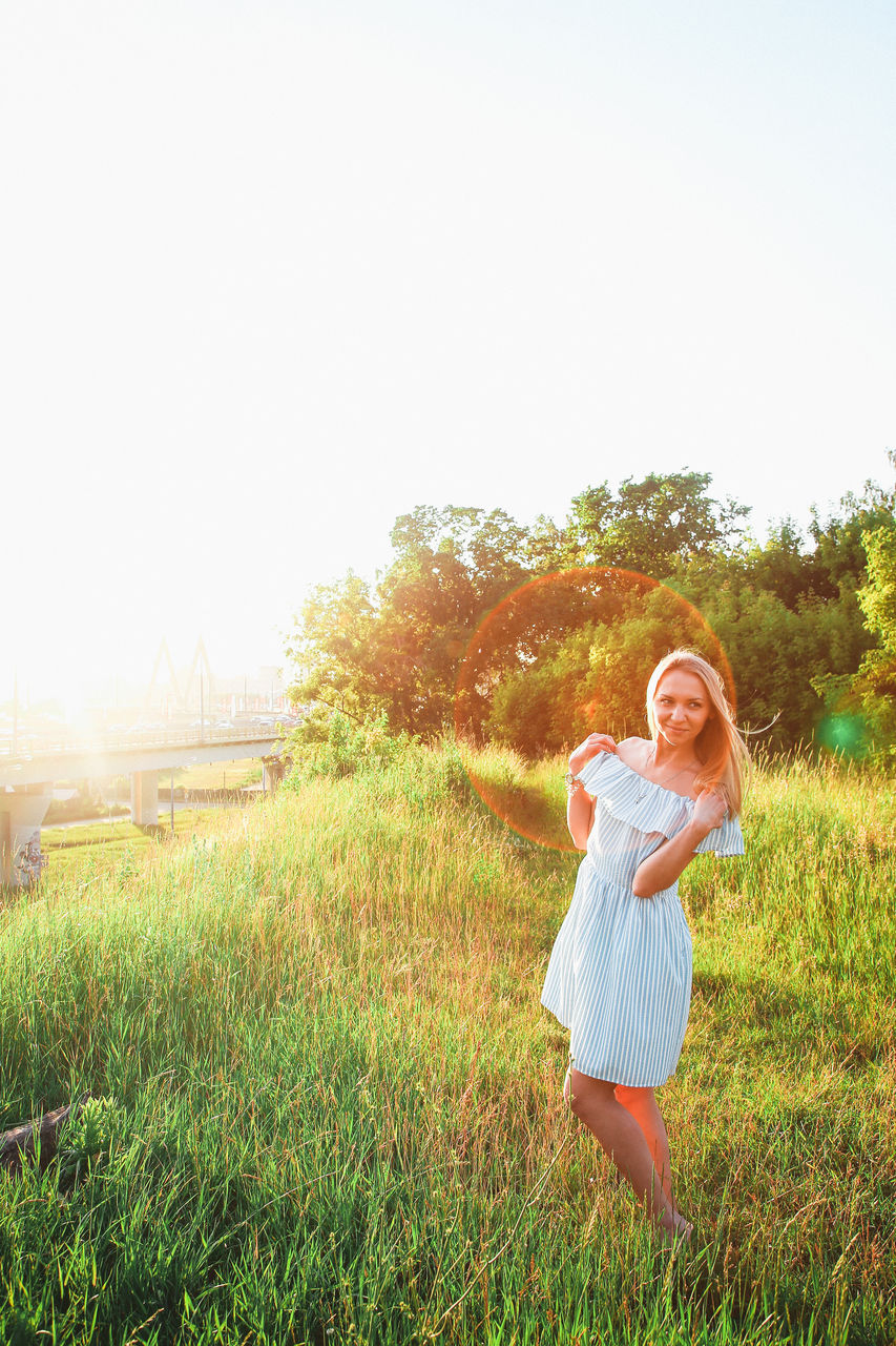Portrait of woman standing on grassy field during sunset