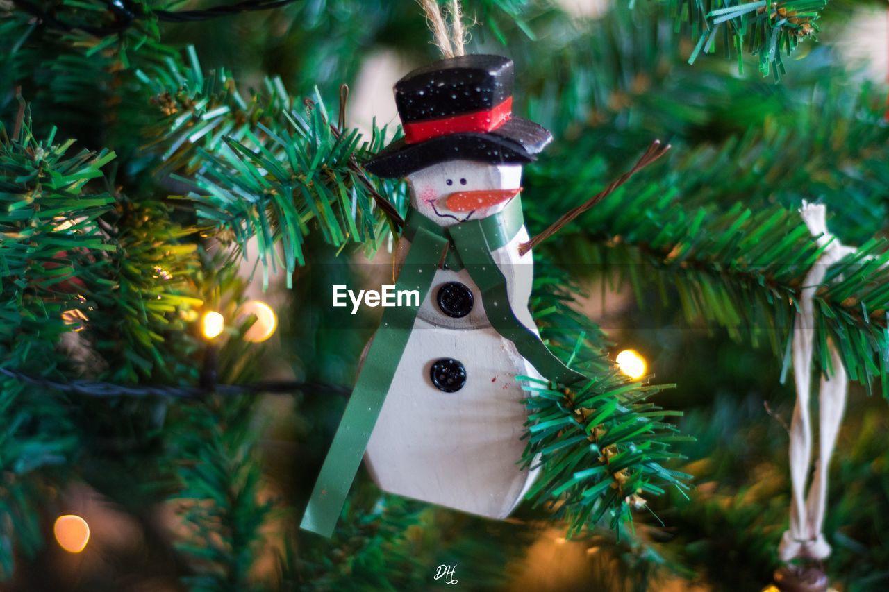 Close-Up Of Snowman Hanging On Illuminated Christmas Tree At Night