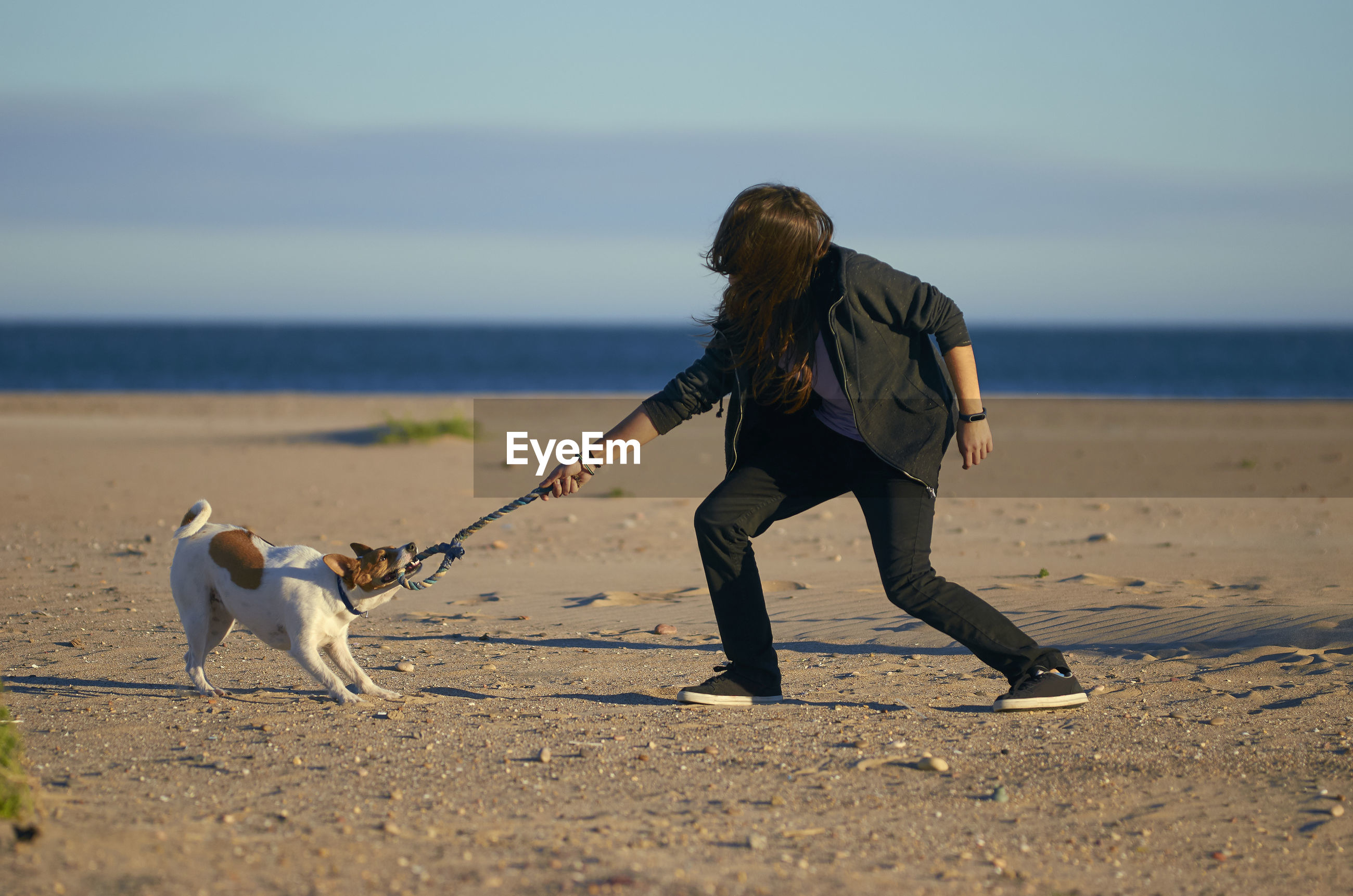 Woman playing with dog at beach against sky