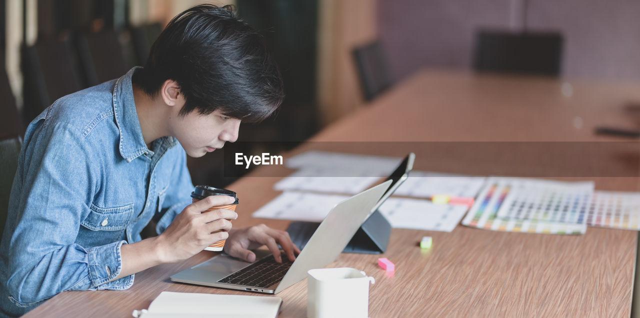 Businessman using laptop on desk in office