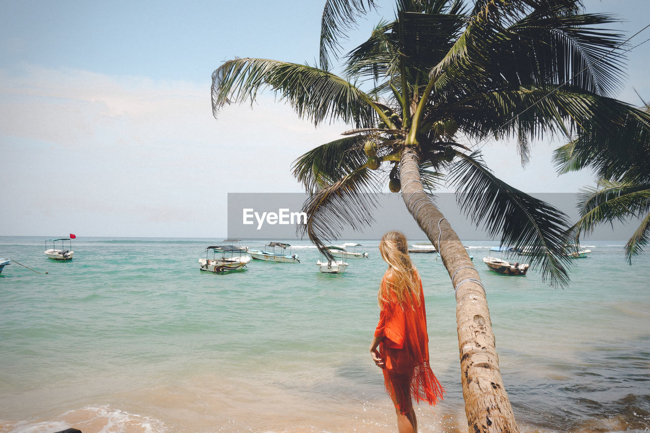 REAR VIEW OF WOMAN STANDING BY PALM TREE AT BEACH