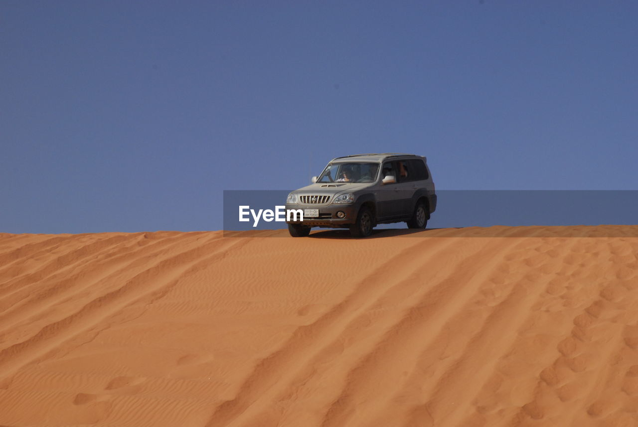 VIEW OF CAR ON SAND DUNE