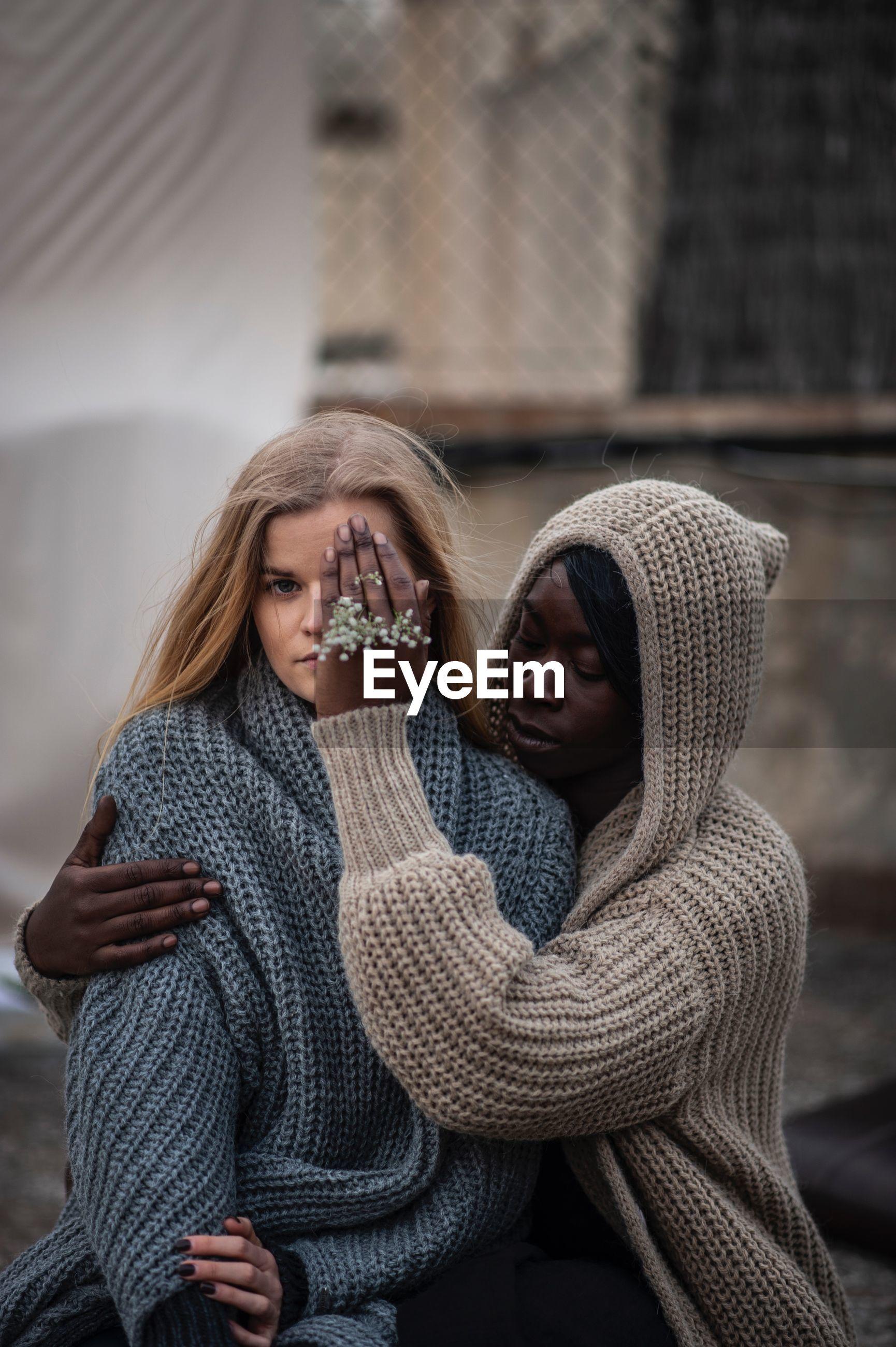 Woman covering friend eye in city