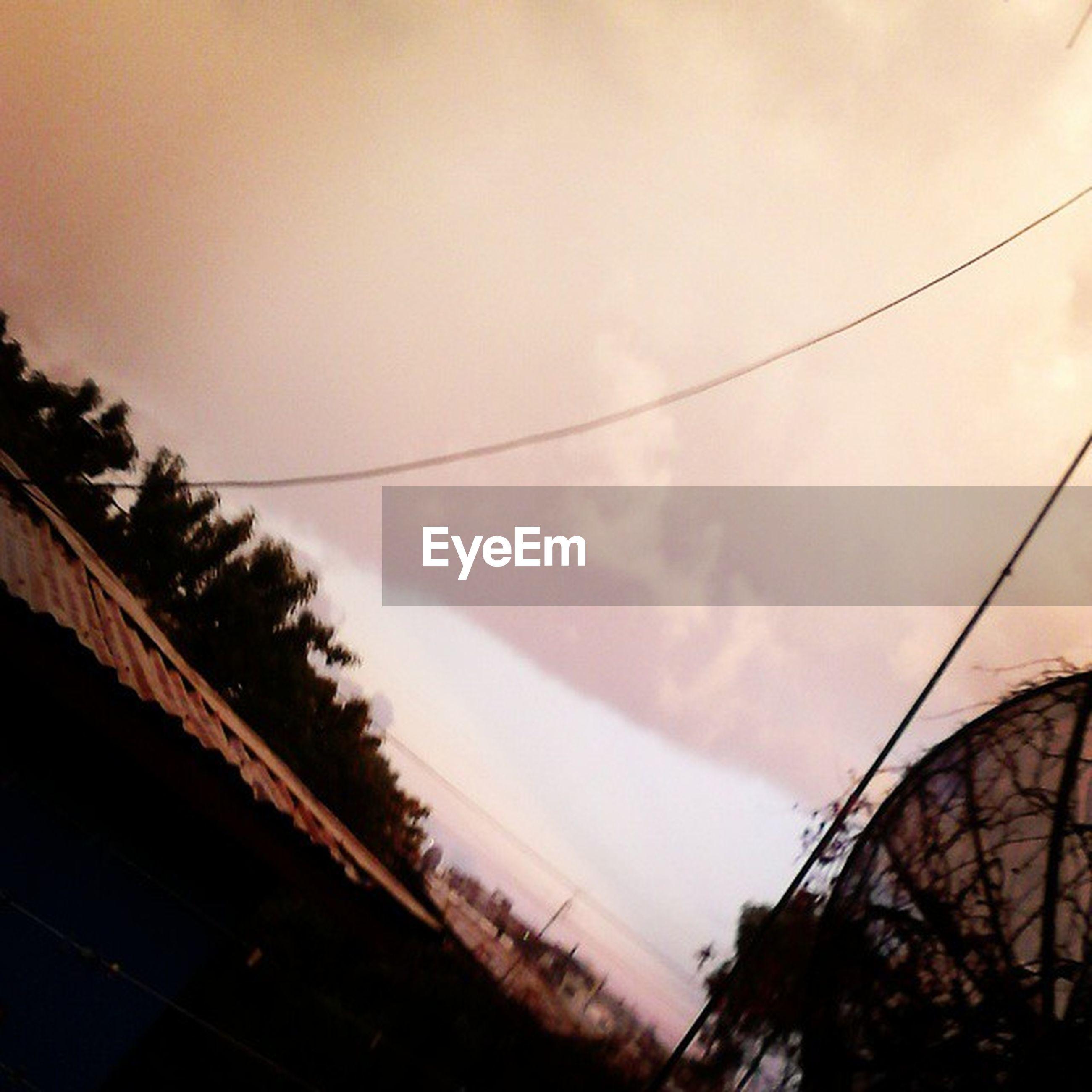 sky, low angle view, power line, built structure, cloud - sky, architecture, dusk, building exterior, silhouette, cable, tree, outdoors, sunset, nature, cloudy, connection, cloud, no people, electricity pylon, transportation