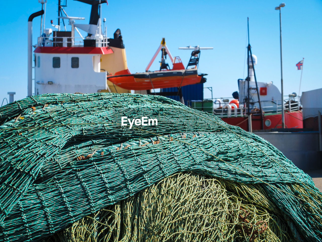 Fishing nets by boats at harbor against sky