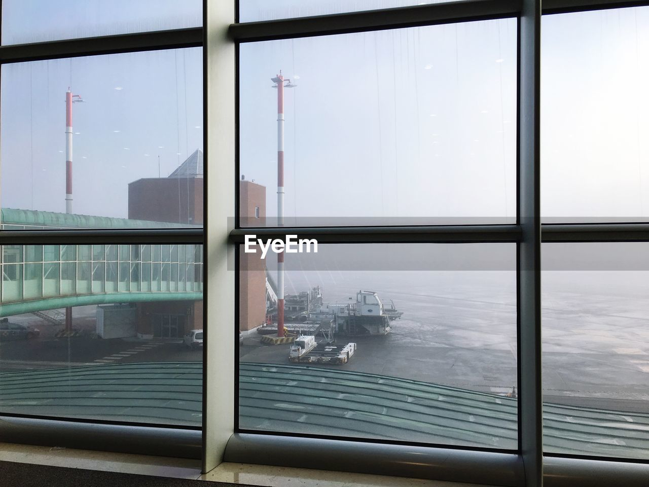Airport runway seen through window during foggy weather