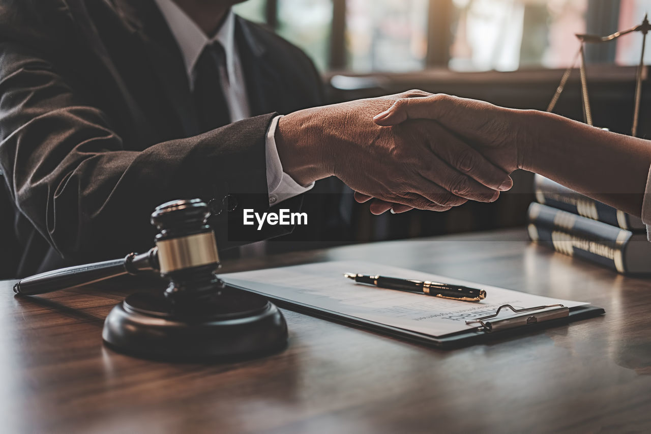 Midsection of judge and client handshaking at table in office