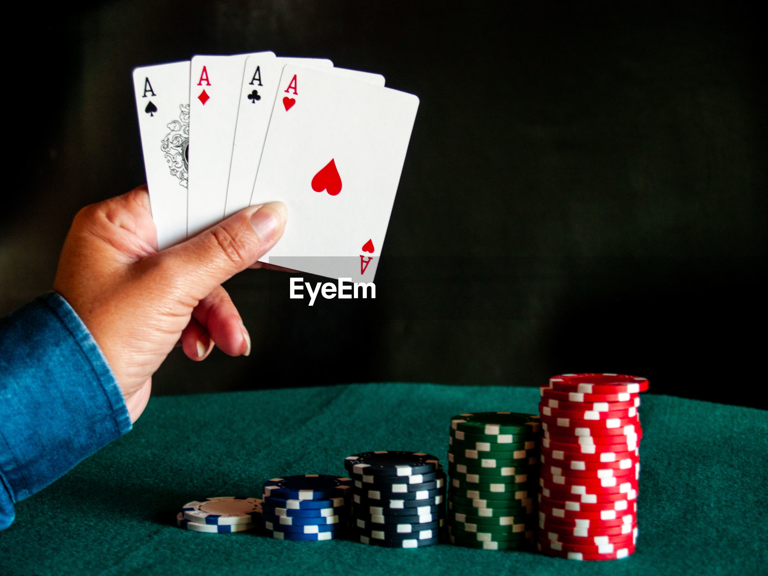 Cropped hand of person holding playing cards with chips in background