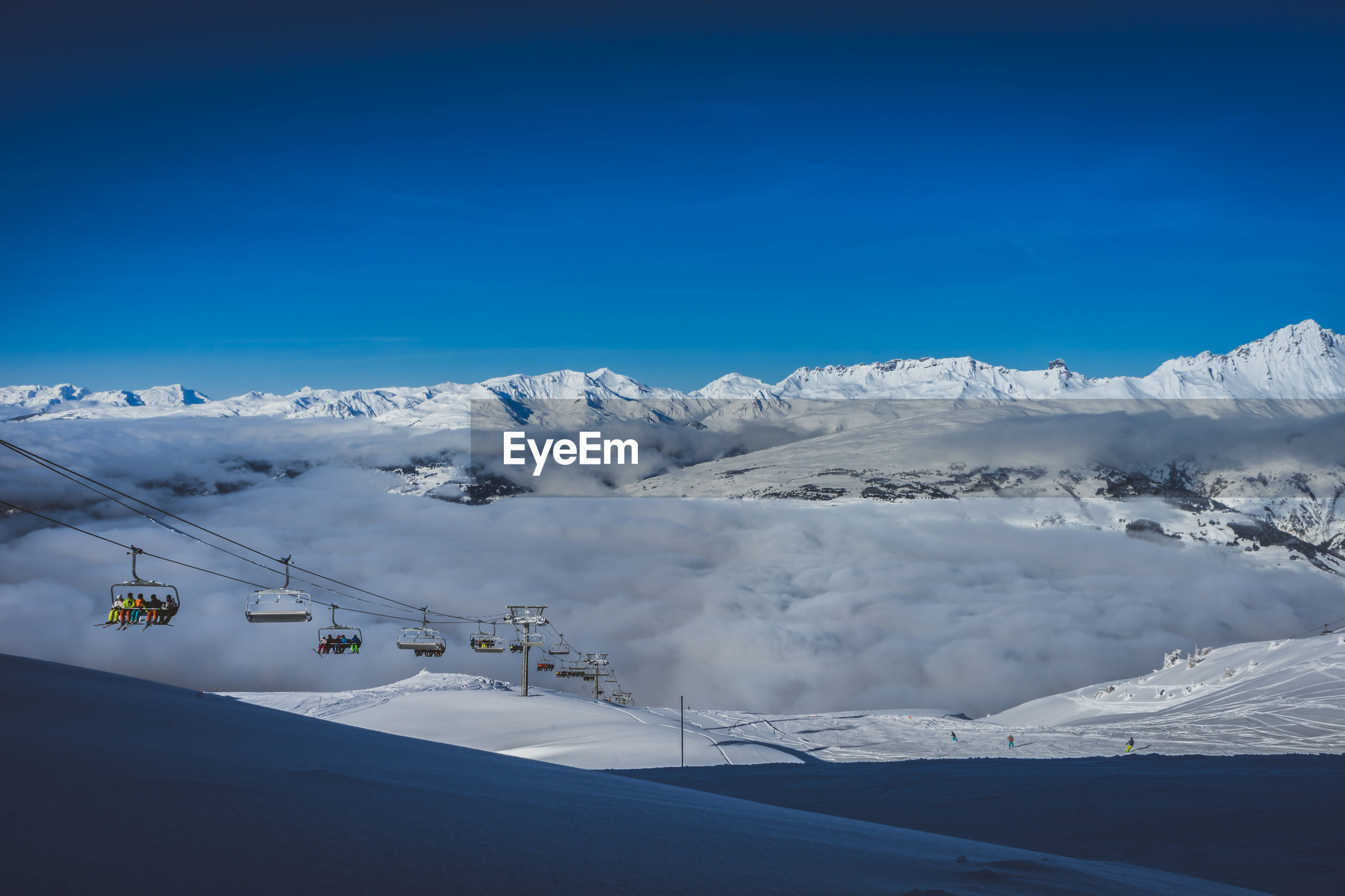 A chairlift rising out of a valley of clouds in les arcs