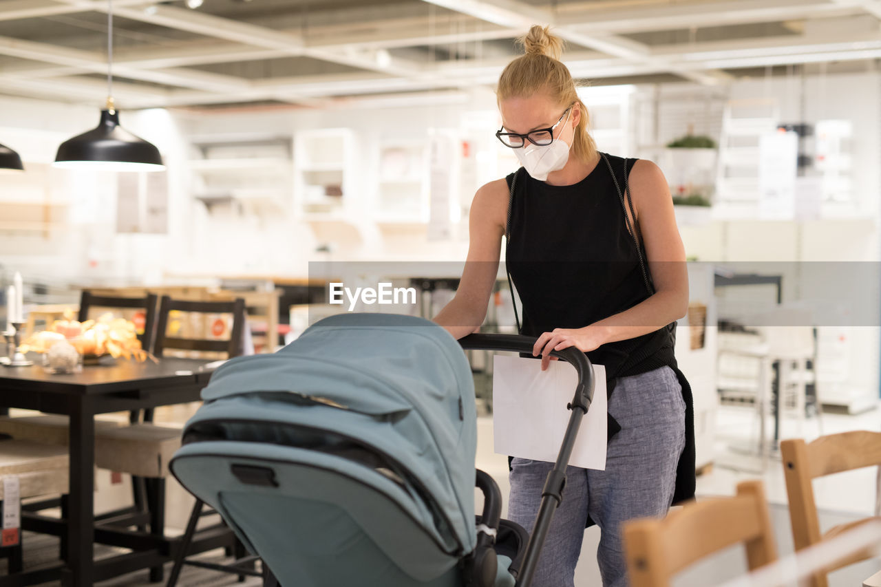 Woman wearing flu mask holding stroller at store