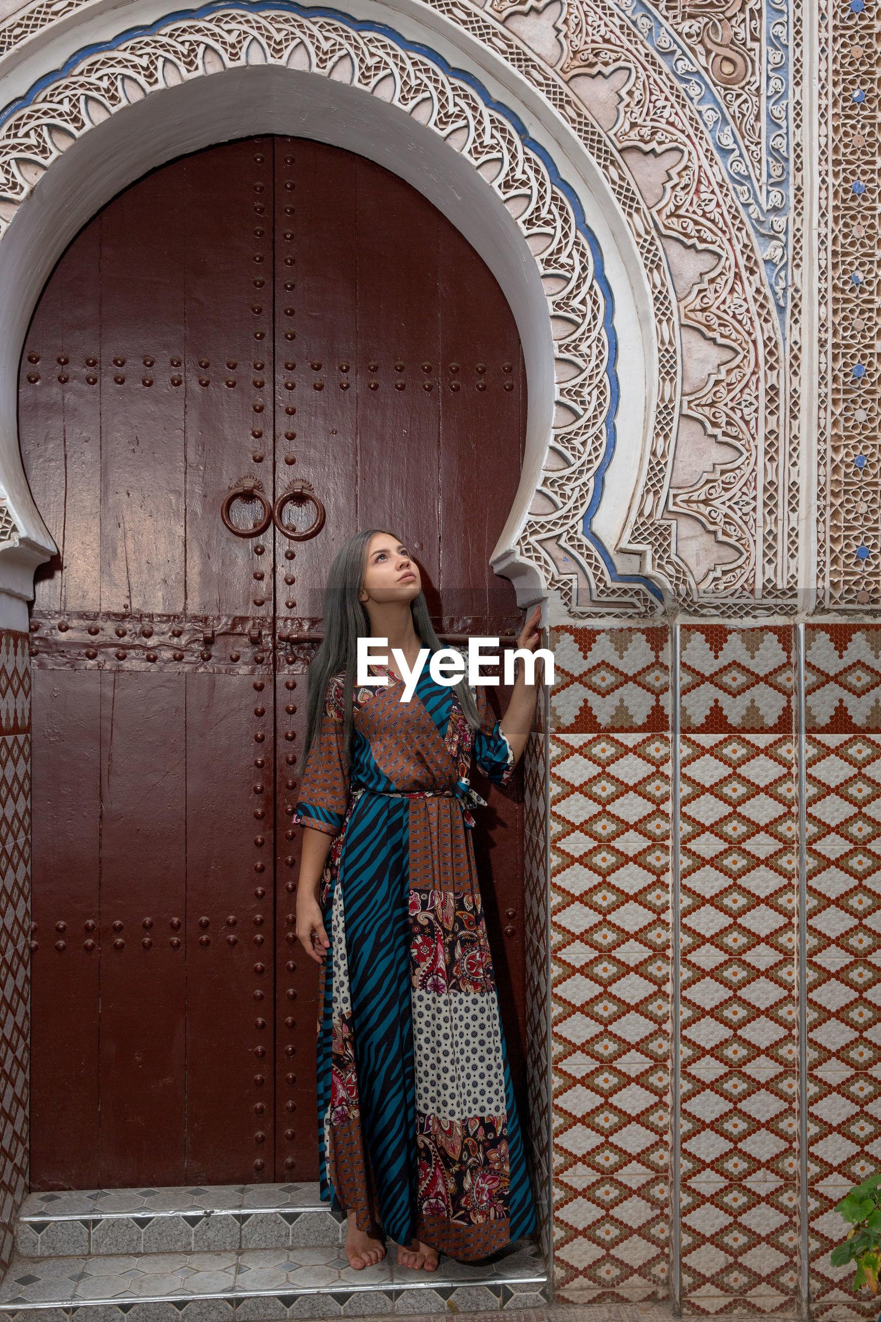 Woman looking away while standing against door of building