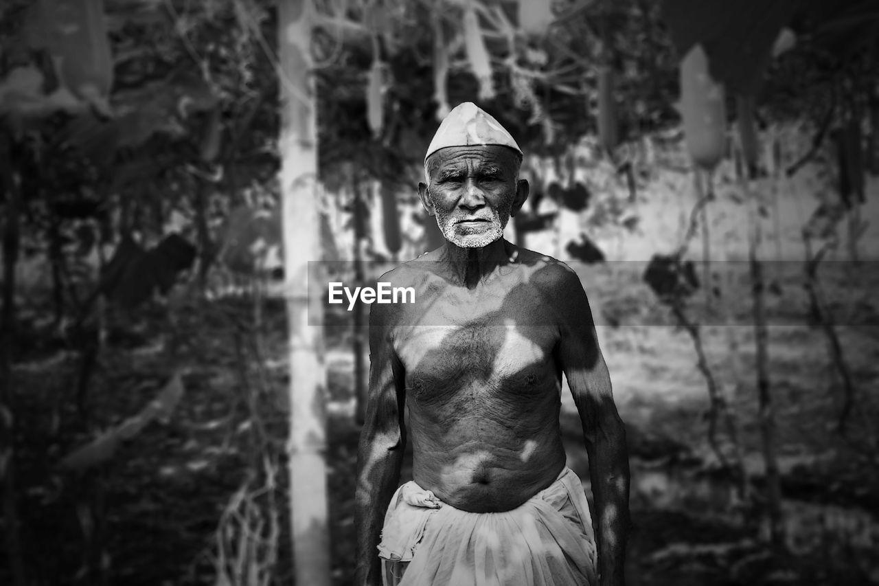 Portrait Of Senior Man Standing Against Trees
