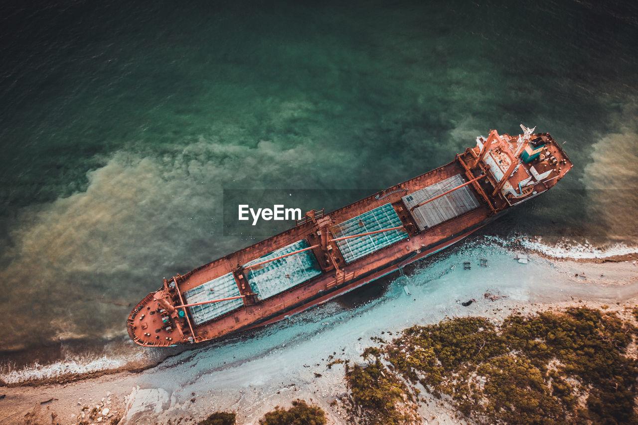 HIGH ANGLE VIEW OF ABANDONED SHIP SAILING ON SEA