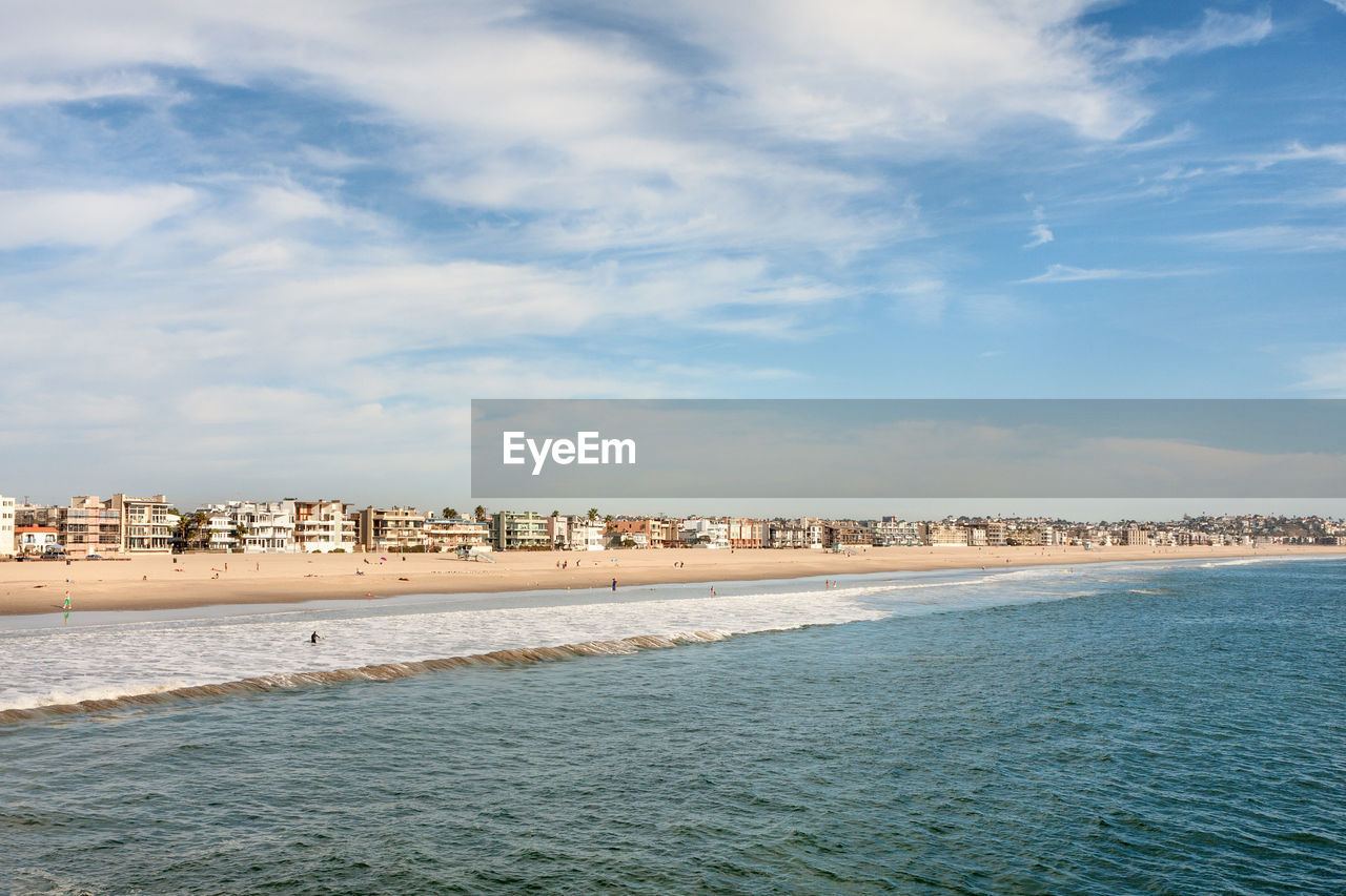 sea, water, sky, cloud - sky, architecture, built structure, beach, building exterior, waterfront, nature, outdoors, beauty in nature, day, scenics, tranquility, no people, sand, wave, travel destinations, city, cityscape