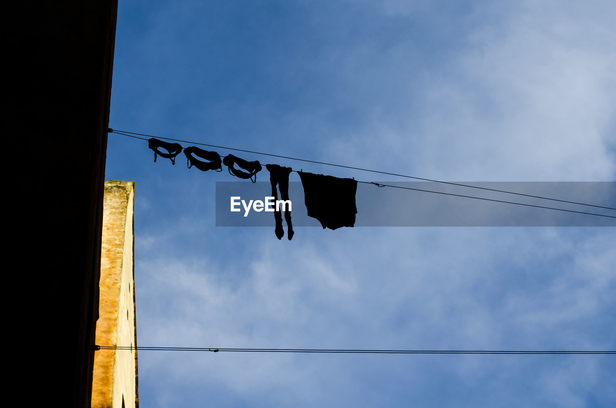 Low angle view of clothesline against sky