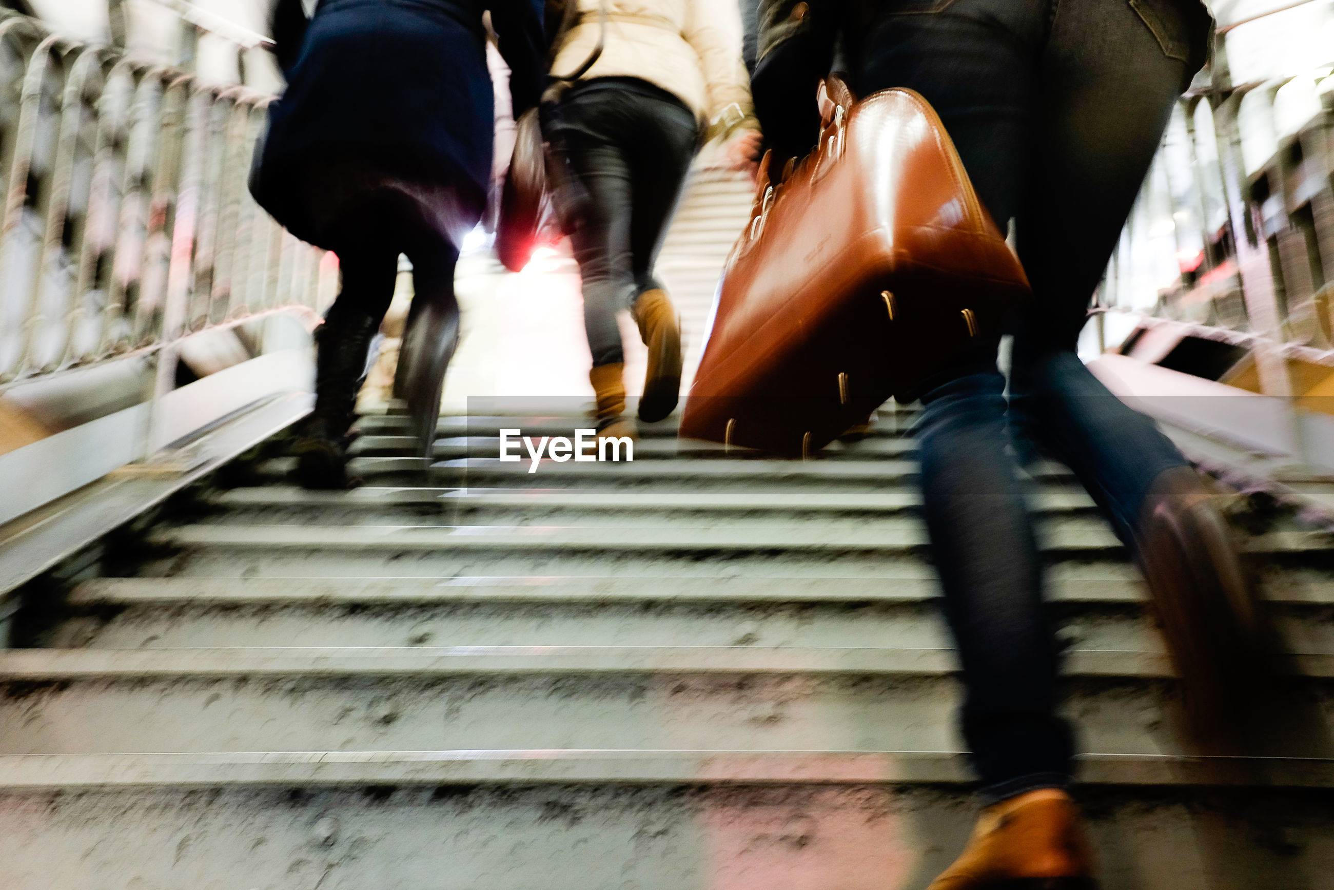 Low section of people walking on staircase