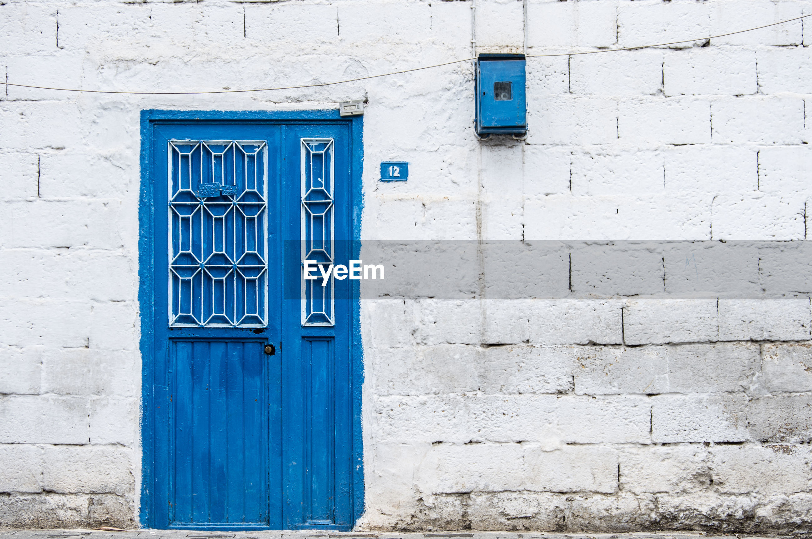 Closed blue door against white concrete wall house