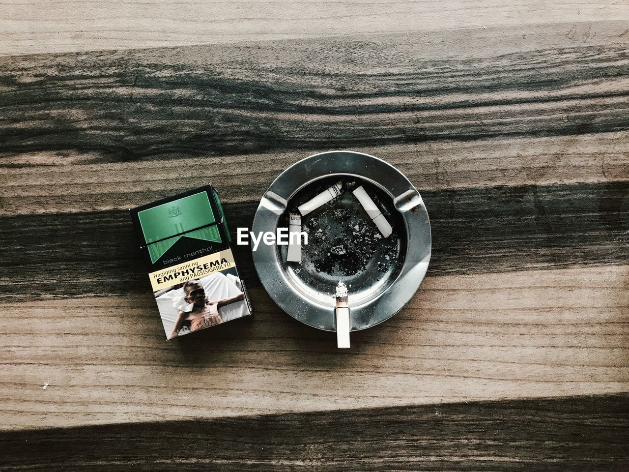 table, bad habit, high angle view, still life, addiction, ashtray, no people, danger, indoors, wood - material, risk, directly above, cigar, close-up, day