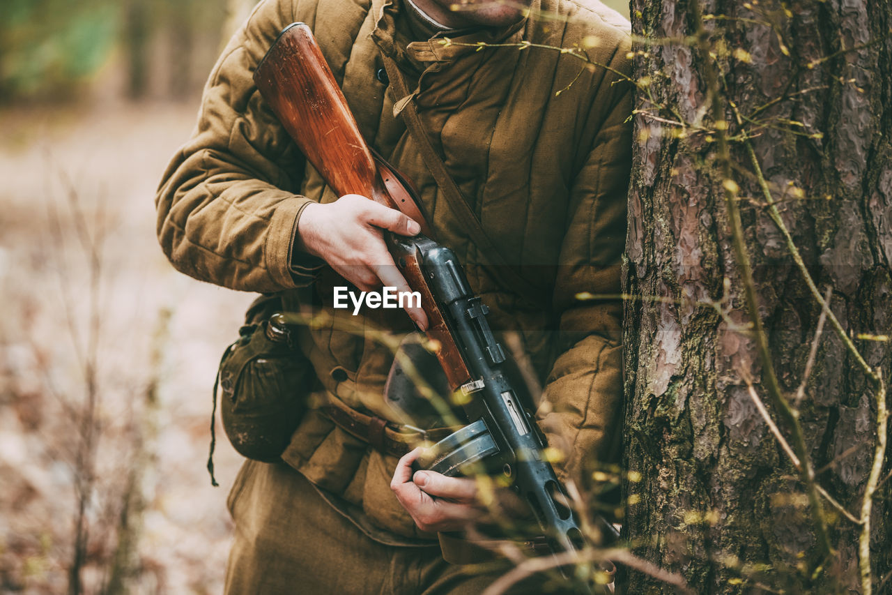one person, real people, holding, tree, weapon, forest, day, land, midsection, focus on foreground, hunting, clothing, plant, rifle, standing, nature, hunter, gun, men, outdoors, skill, uniform, government